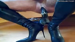 freak pumps his cock while riding a dildo in boots