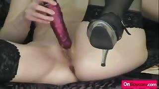 Blonde slut playing with long dildo on couch